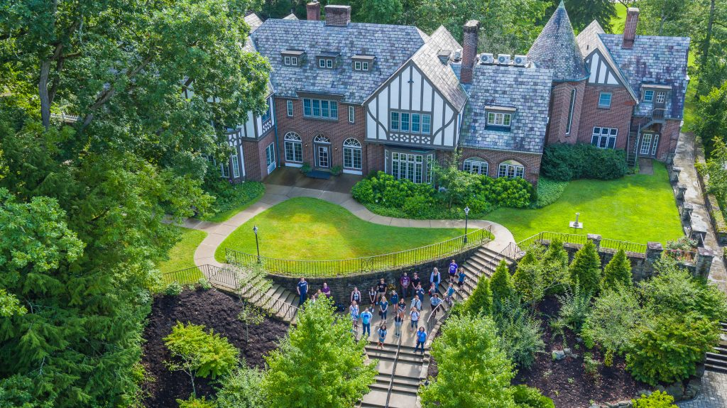 Aerial shot of Alpha 2017 students on the UPG campus. The students are standing on the sidewalk in front of a brick building with sloping gray tiled roofs, which is surrounded by shrubs and trees.